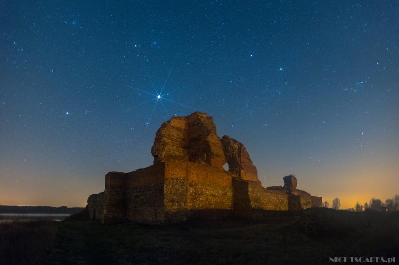 Jowisz świecący nadruinami zamku wBobrownikach nocą