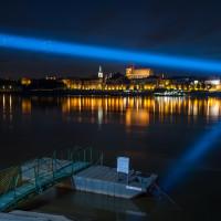Most świetlny na tle panoramy starówki w Toruniu.