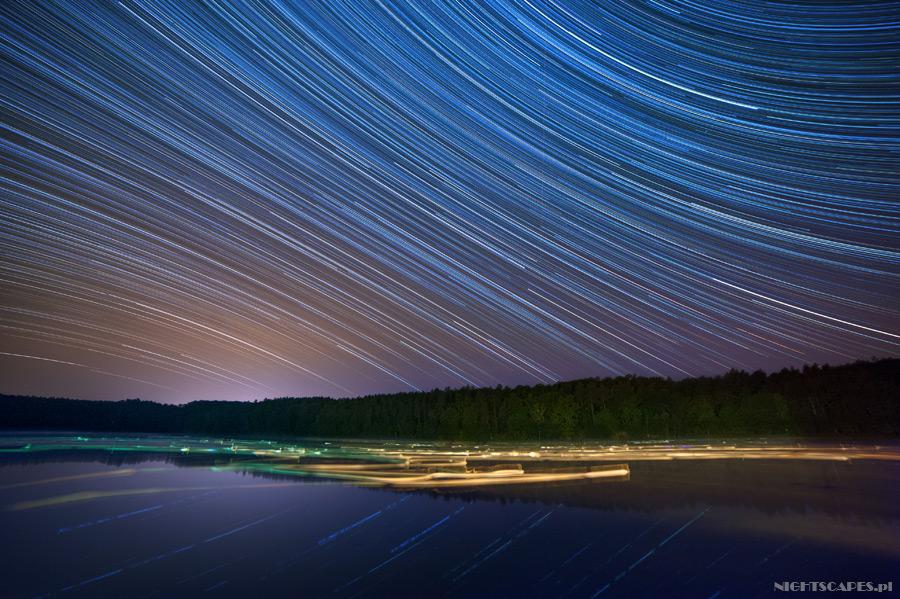 Ślady gwiazd nadJeziorem Bachotek wjesiennej scenerii